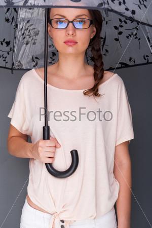 Фотография на тему Молодая женщина с модным зонтом стоит на сером фоне