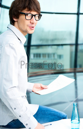 Творческий деловой человек сидит с бумагами на столе в офисе