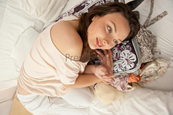 Портрет молодой женщины, готовящейся к поездке или распаковывающей чемодан