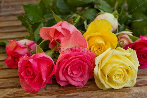 Букет из роз в каплях воды на деревянном столе