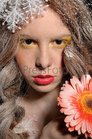 Красивая девушка с цветком в руке со снежинками