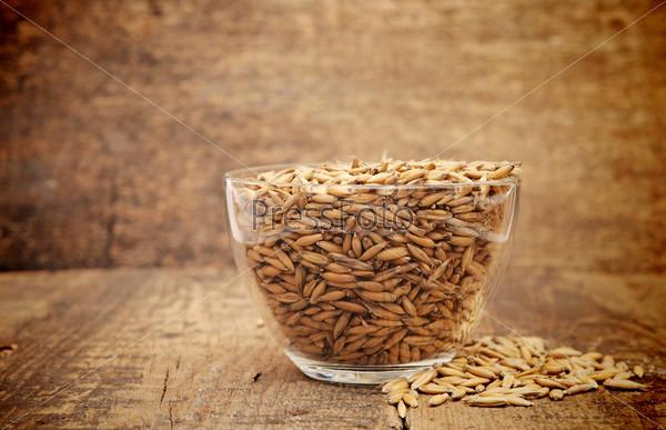 Овсяные зерна в стеклянной чаше на деревянном столе
