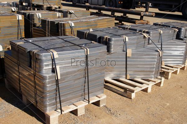 Упакованные металлические детали на поддонах на складе