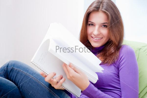 Молодая женщина с тетрадью в домашней обстановке