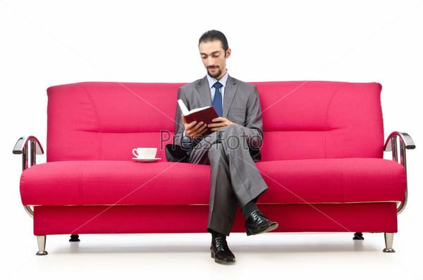 Молодой человек, сидящий на диване