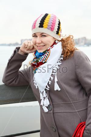 Портрет счастливой девушки с красной сумкой, стоящей на набережной