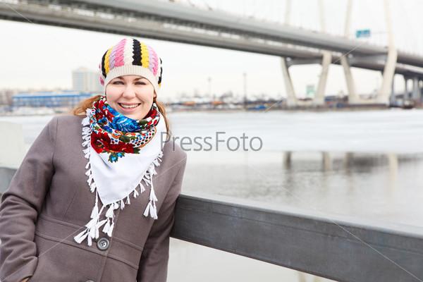 Портрет счастливой девушки в шарфе, стоящей на набережной