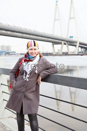 Фотография на тему Портрет счастливой девушки с красной сумкой, стоящей на набережной
