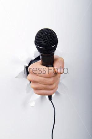 Рука с микрофоном через отверстие в бумаге