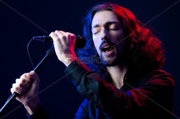 Молодой человек поет на концерте