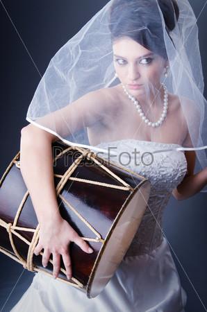 Невеста в свадебном платье играет на барабане