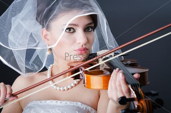 Невеста в свадебном платье играет на скрипке  в студии