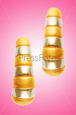 Две желтые серьги на розовом фоне