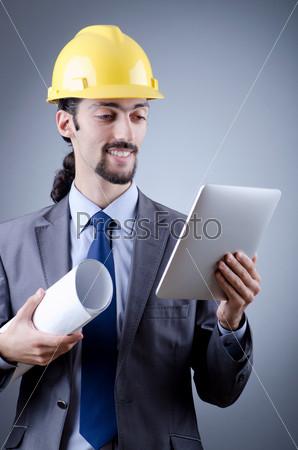 Фотография на тему Инженер-строитель с планшетным компьютером в руке