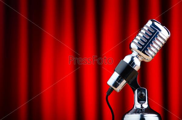 Студийный микрофон на фоне красного занавеса