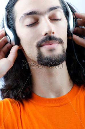Студент в наушниках слушает музыку