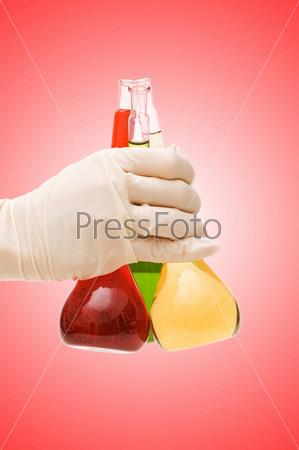 Рука с химическими колбами на фоне градиента