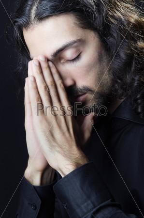 Молодой человек молиться в темноте