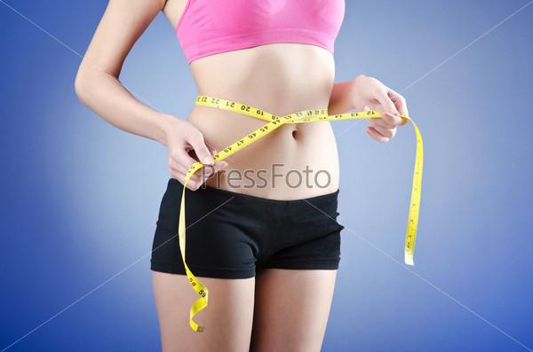 Фотография на тему Молодая женщина измеряет обхват талии, концепция диеты