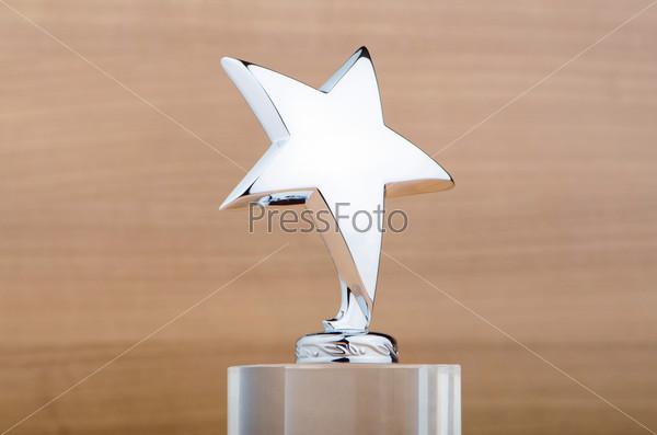 Премия в форме звезды на деревянном фоне