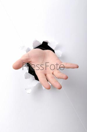Фотография на тему Рука через отверстие в бумаге