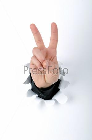 Рука через отверстие в бумаге