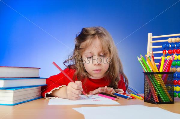 Маленькая девочка, рисующая карандашами
