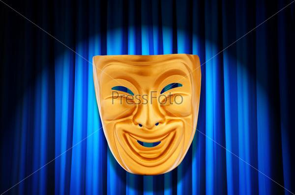 Золотая маска на фоне освещенных театральных кулис