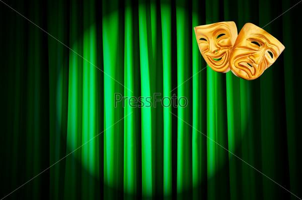 Золотые театральные маски на фоне зеленых кулис