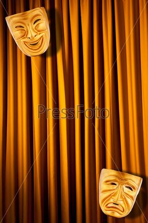 Две золотые театральные маски на фоне желтых кулис