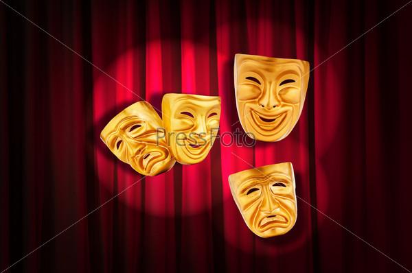 Фотография на тему Четыре золотые театральные маски на фоне освещенных красных кулис