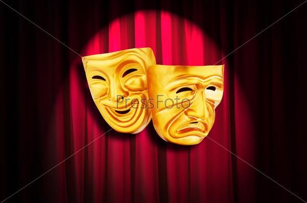 Две золотые театральные маски на фоне освещенных красных кулис