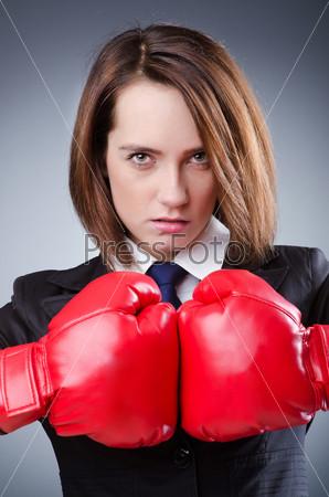 Молодая женщина в мужском деловом костюме и в красных боксерских перчатках на сером фоне