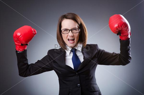 Боевая женщина в мужском деловом костюме и в красных боксерских перчатках на сером фоне