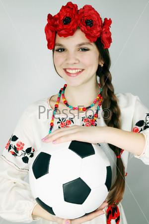 Девушка в украинском костюме держит в руках футбольный мяч