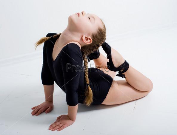 Девочка занимается гимнастикой на белом фоне