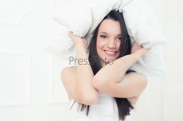 Фотография на тему Счастливая молодая женщина в постели с подушкой