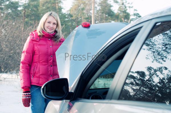 Молодая блондинка стоит возле автомобиля с открытым капотом