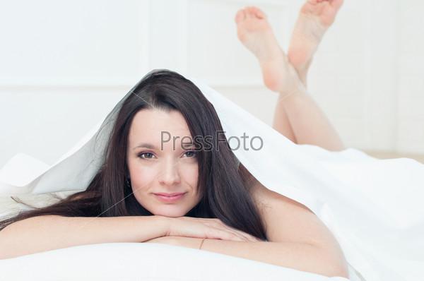 Молодая темноволосая женщина лежит в постели и смотрит в камеру
