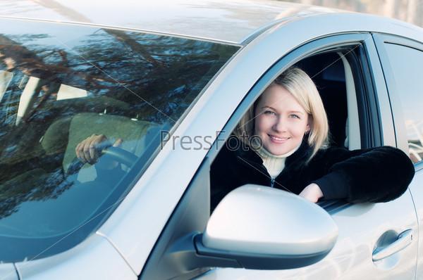 Улыбающаяся блондинка за рулем автомобиля