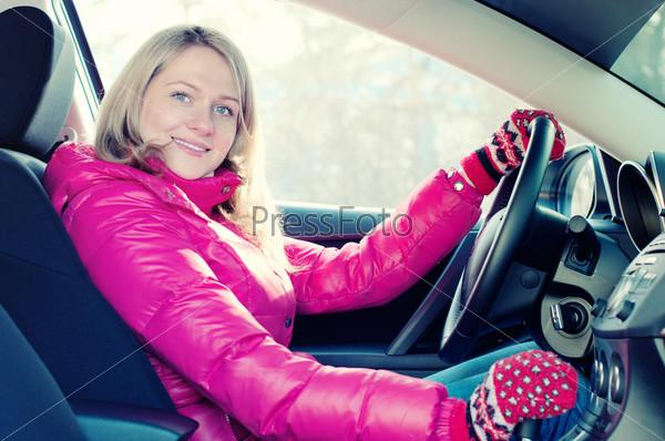 Улыбающаяся белокурая женщина сидит за рулем автомобиля