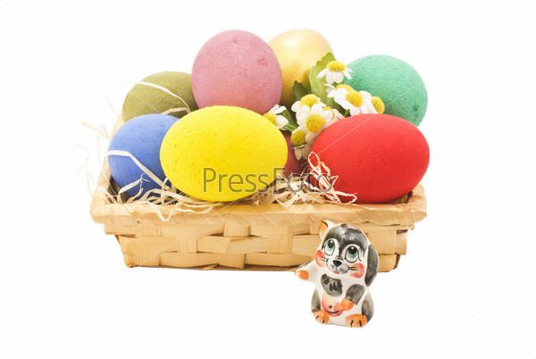 Разноцветные яйца в корзине и фигурка кролика