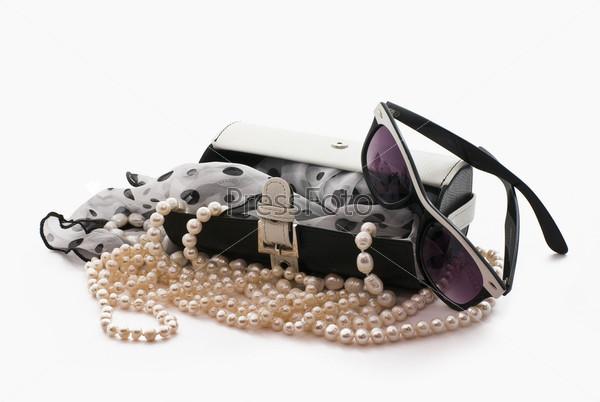 Сумочка, шарф, солнцезащитные очки и жемчуг на белом фоне