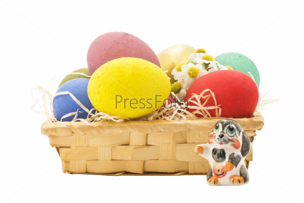 Яйца в корзине и фарфоровая фигурка кролика  на белом фоне