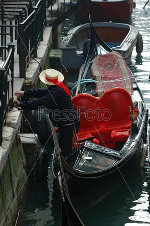 Гондольер подает лодку для туристической прогулки на каналах Венеции