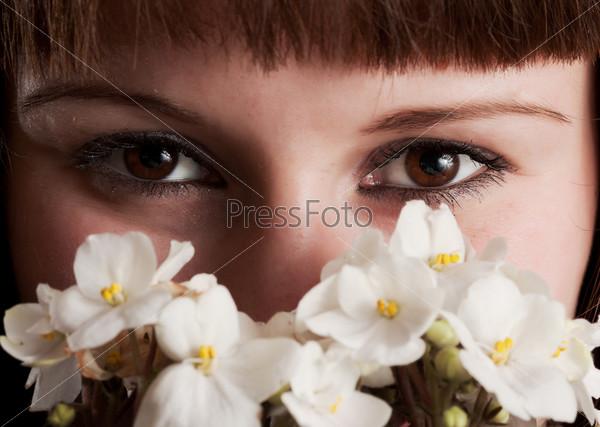 Фотография на тему Лицо кареглазой девушки с букетом белых фиалок