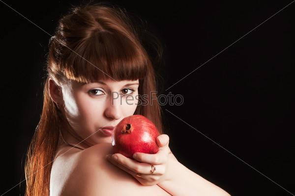 Сексуальная девушка с гранатом на черном фоне