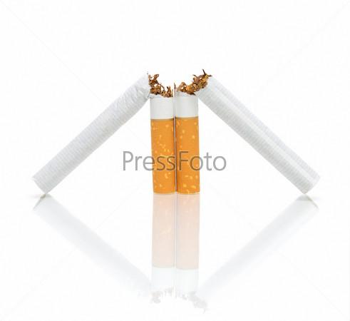 Две сломанные сигареты на белом фоне с отражением