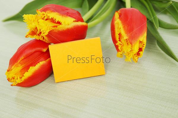 Букет оранжевых тюльпанов с пустой карточкой на столе