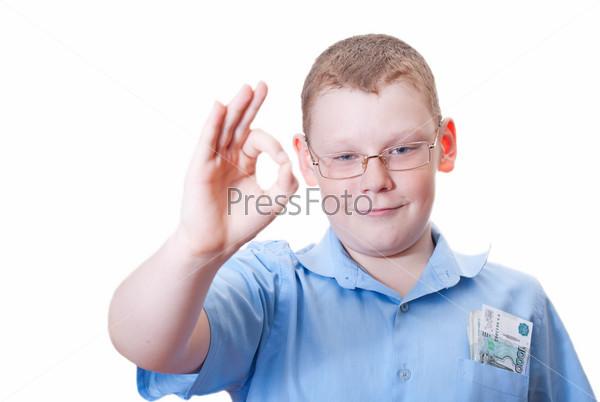 Довольный мальчик с деньгами в нагрудном кармане показывает жест ОК на белом фоне